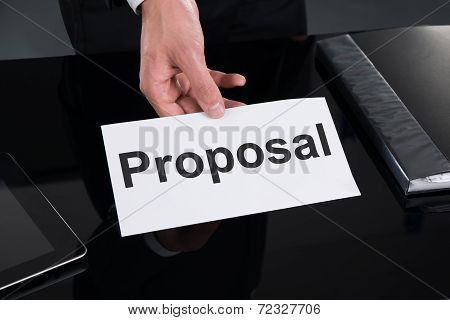 Businessman Holding Proposal Sign At Desk