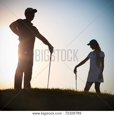 Male And Female Golfers At Sunset