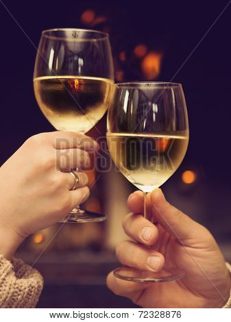 Couple Toasting Wineglasses In Front Of Lit Fireplace