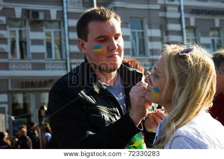 Peace March, participants draw on their faces, Ukrainian flag