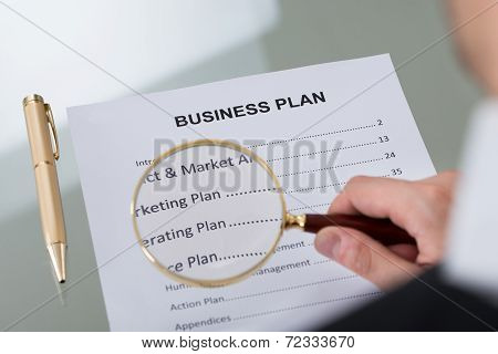 Businessman Examining Business Plan With Magnifying Glass