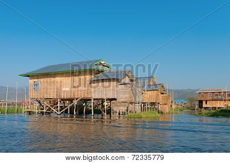 Traditional Stilts House In Water Under Blue Sky