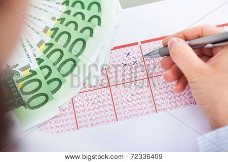 Hand With Lottery Ticket And Banknotes