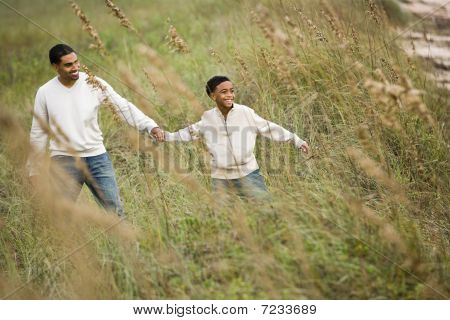 African-American father and son walking through sea oats grass at beach