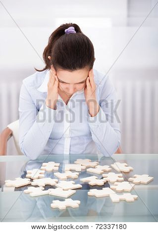Businesswoman With Puzzle At Desk