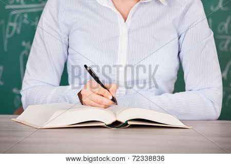 Student Reading Textbook At Desk