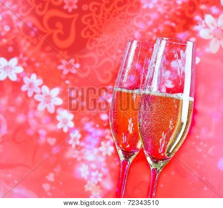 Champagne Flutes With Golden Bubbles On Red Vintage Background