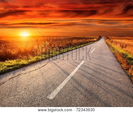 Driving On An Empty Road At Sunset