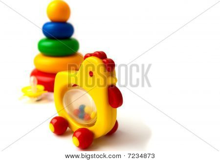 Children's toys a pyramid, a chicken a rattle and a yellow dummy