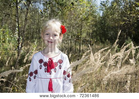 In The Autumn Forest On A Glade Little Blonde Girl Standing Dressed In Embroidered In High Grass.