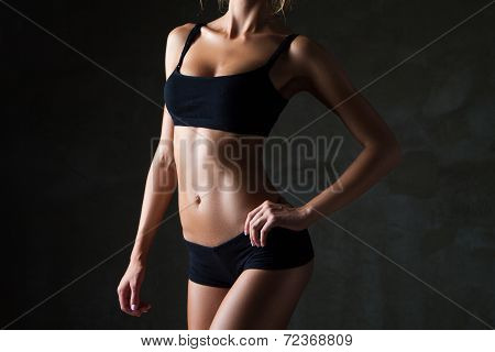 Slim woman's body  over dark gray background