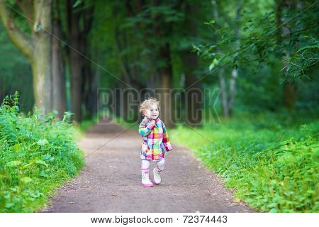 Funny Curly Baby Girl In Rain Boots Walking In A Park