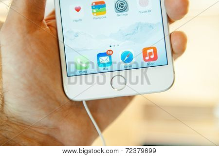 Hand holding a iPhone 6 Plus displaying the Touch Id button