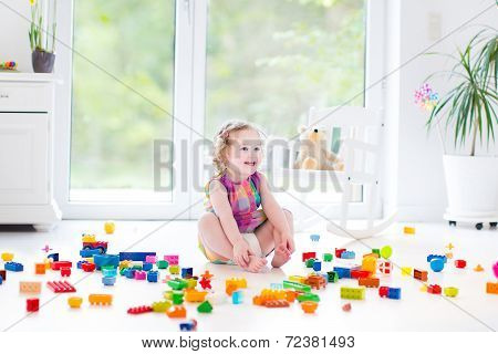 Cute Laughing Toddler Girl Playing With Colorful Blocks Sitting On A Floor In A Sunny Bedroom
