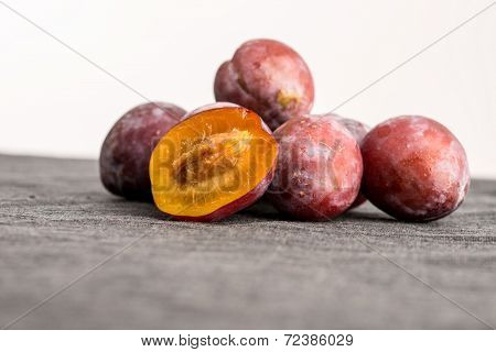 Heap Of Fresh Plums With One Halved