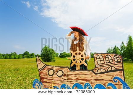 Girl as pirate holds helm and bends her arm