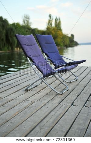 Two Blue Folding Chairs On A Wooden Platform On The River