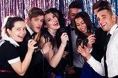 picture of karaoke  - Portrait of happy multiethnic friends singing into microphones at karaoke party - JPG