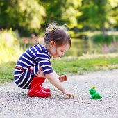 Постер, плакат: Beautiful Little Girl In Red Rain Boots Playing With Rubber Frog