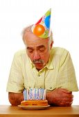 picture of birthday-cake  - Elderly man blowing out a large number of candles on a birthday cake - JPG