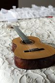 stock photo of low-necked  - Spanish classical guitar lying on the bed - JPG