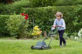 image of grass-cutter  - Little Boy Playing With A Lawn Mower In The Garden - JPG