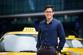 foto of driver  - Portrait of happy chinese taxi driver leaning on yellow car with arms crossed smiling and looking at camera - JPG