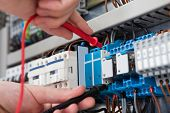 image of fuse-box  - Closeup of male electrician examining fusebox with multimeter probe - JPG