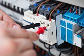 picture of electrician  - Closeup of male electrician examining fusebox with multimeter probe - JPG
