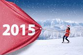 picture of rope pulling  - Attractive woman wearing santa hat and pulling number of 2015 in winter - JPG