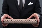 stock photo of entrepreneurship  - Midsection of businessman showing Entrepreneurship blocks arranged on desk - JPG
