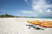stock photo of humiliation  - Kayaks on tropical beach under blue sky with cumulus humilis cloud - JPG