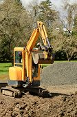 picture of track-hoe  - Construction contractor using a small track hoe excavator to dig a water line trench on a new commercial residential development - JPG