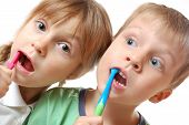 stock photo of grils  - two cute kids brushing their teeth over white background - JPG