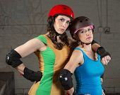 stock photo of roller-derby  - Confident female roller derby skating partners standing together - JPG
