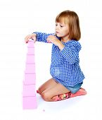 picture of cylinder pyramid  - Very passionate little girl collects Montessori pyramid - JPG