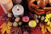 stock photo of centerpiece  - Happy Halloween party table centerpiece with orange glitter jack-o-lantern pumpkin with lit candles and autumn Fall leaves nuts and berries on black tablecloth. Closeup.