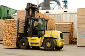 foto of lumber  - Large lift truck moving a stack of green fir 2 x 4 lumber studs at a small log processing mill in southern Oregon ready for the drying kiln - JPG