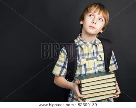 Portrait of diligent student in glasses with heap of books in hands