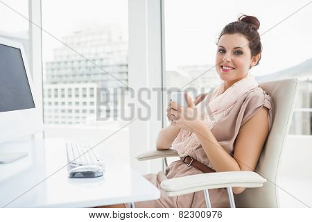 Relaxed businesswoman holding hot drink in the office