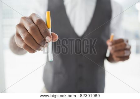 Businessman holding electronic cigarette and cigarette in the office