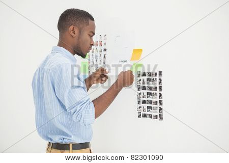 Concentrated businessman standing and reading document in the office
