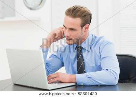 Smiling businessman making a call at his desk in his office