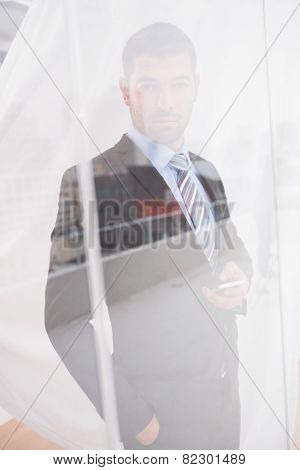 Serious businessman holding phone looking at camera in his office