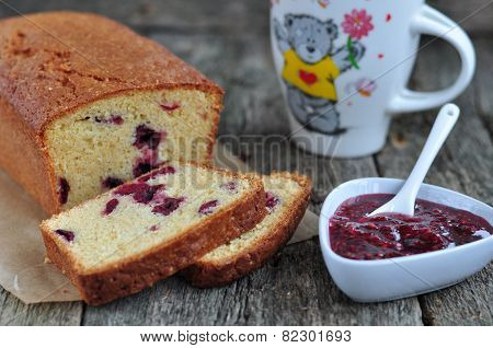 Cup of coffee or tea with a cherry cake on a wooden dinner-table