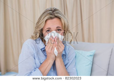 Sick blonde on couch sneezing on tissue at home in the living room