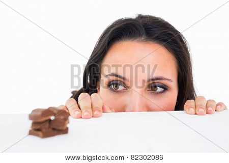 Pretty brunette peeking at chocolate on white background