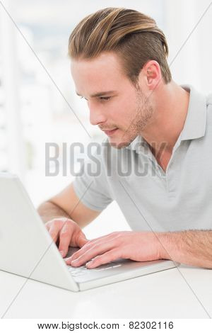 Concentrated businessman typing on laptop in his office