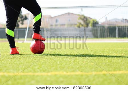 Soccer Player with Black Sweats Look at Goal with Red Soccer Ball on Green Field