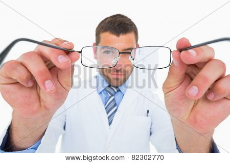 Smiling optician presenting eyeglasses on white background